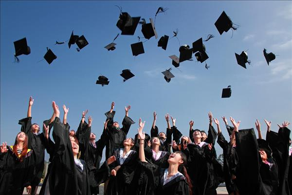 Students in graduation gowns tossing their hats into the blue sky